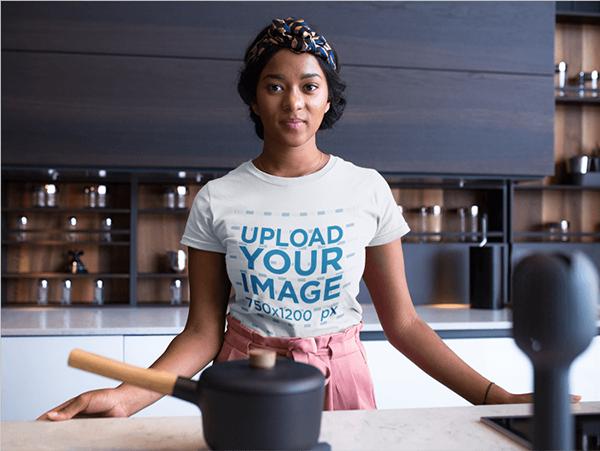 Mujer vistiendo una maqueta de camiseta de cuello redondo mientras está en la encimera de su cocina