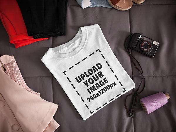 Maqueta de camiseta doblada junto a una cámara y ropa en una cama